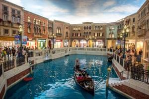 Tourists take a gondola ride inside The Venetian.