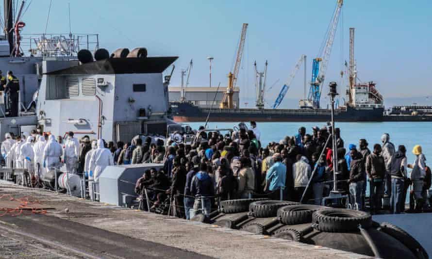 Rescued migrants wait to disembark off the Italian Guardia di Finanza vessel Denaro at the Sicilian harbour of Catania.