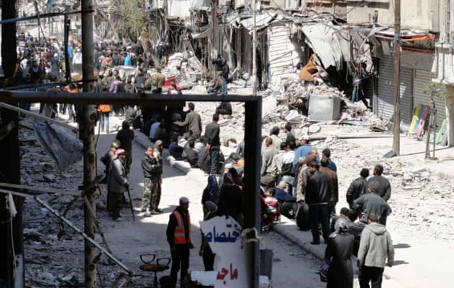 01 Apr 2014, Damascus, Syria --- Residents wait to receive food aid distributed by the Al-Wafaa campaign at the Palestinian refugee camp of Yarmouk, south of Damascus April 1, 2014.