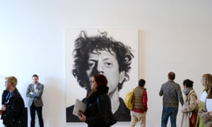 People walk past a Chuck Close portrait at the press preview.