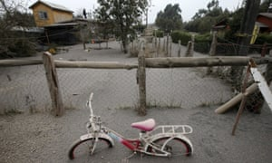 A child's bicycle shows the depth of ash from the Calbuco volcano blanketing the ground.