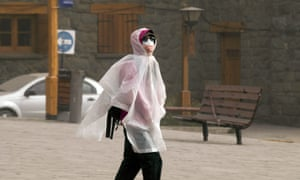 A woman walks in a street covered in ash in Bariloche, Argentina.