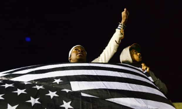 Protesters display a flag as demonstrations continue  over Freddie Gray's death in Baltimore police custody.
