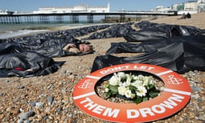 Protesters from Amnesty International in body bags on Brighton beach