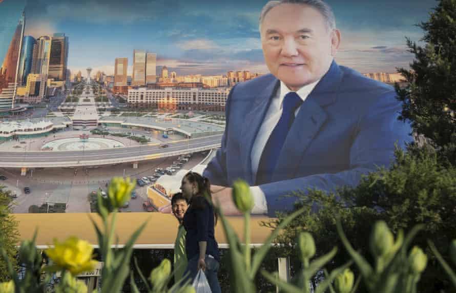 People walk past an election banner for Kazakhstan's president, Nursultan Nazarbayev, in Almaty.