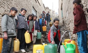 Children fill cans with drinking water from a community tap in Kabul
