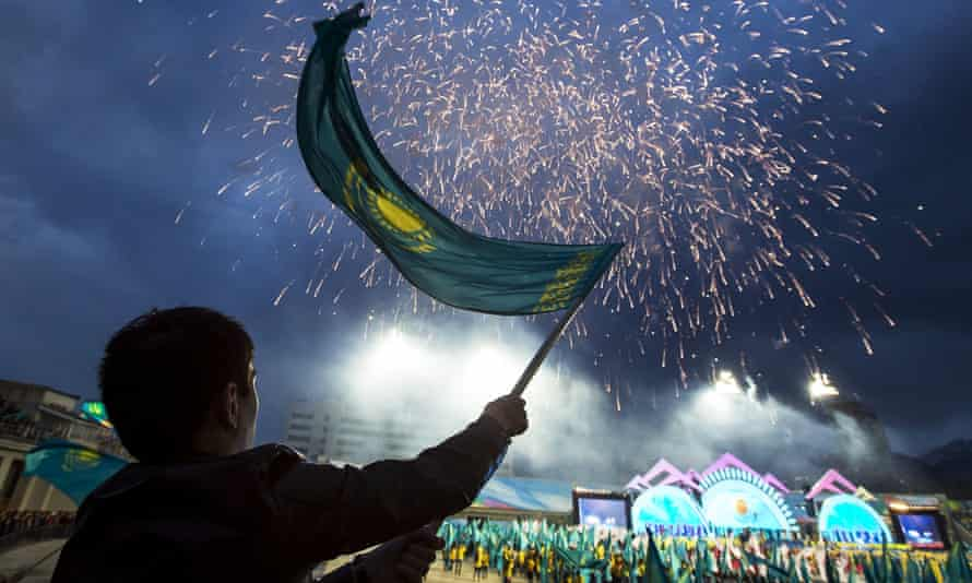 A man waves a national flag during a campaign rally for Nursultan Nazarbayev at a stadium in Almaty.