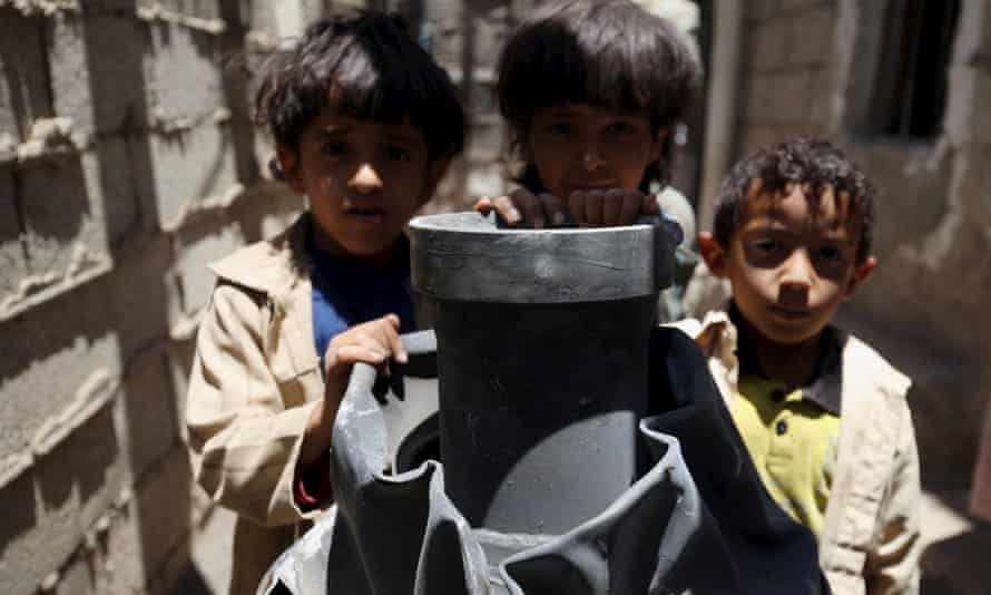 Children stand next to a shell which landed on their house from a nearby missile base after the base was struck by a Saudi-led coalition air strike, near Sanaa April 23, 2015.
