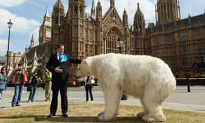 A David Cameron lookalike poses with a polar bear model outside the parliament as part of a Greenpeace protest