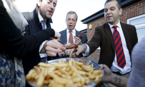 Nigel Farage and reporters eat sausages during a visit to mark St George's Day in Ramsgate.