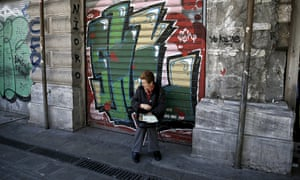 A woman selling lottery tickets outside a closed shop in central Athens.