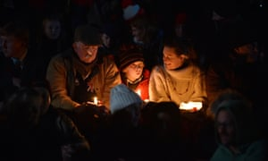 People hold candles in remembrance at the dawn service in Canberra.