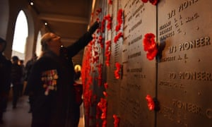 A woman places a poppy on the wall of remembrance after the dawn service at the Australian War Memorial in Canberra.