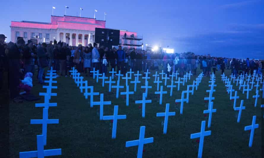 People stand behind crosses for the fallen at the Auckland War Memorial Museum on Anzac Day.