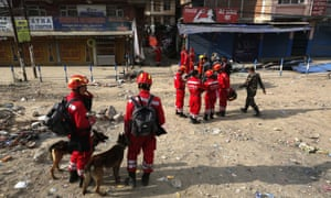 A Chinese rescue team with sniffer dogs wait at the site of a building damaged in  Saturday's earthquake in Kathmandu.