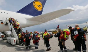 Members of Germany's International Search and Rescue (ISAR-Germany) NGO board their flight to Nepal at Frankfurt airport.