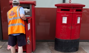 A postal worker empties a postbox in London