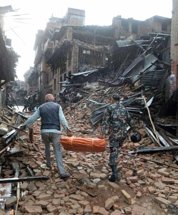 A Nepalese volunteer and member of the security forces carry tents to be distributed in Bhaktapur on Sunday.