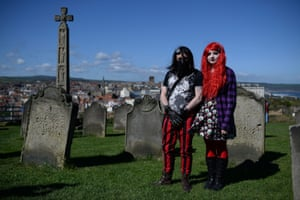 Gothic characters pose for a photograph at a cemetery during the Goth festival in Whitby, North Yorkshire, north east England