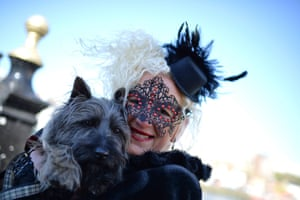 A Gothic character poses for a photograph with her dog during the Goth festival in Whitby, North Yorkshire