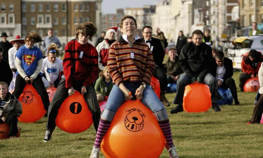 people bounce on orange Spacehoppers