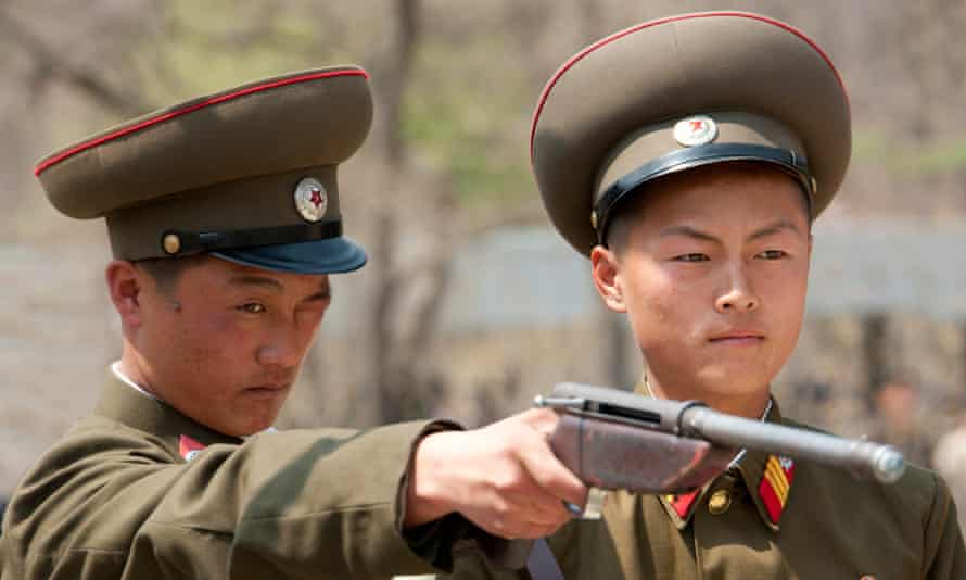 Two members of the Korean People's Army have a go on a firing range at a fair in Pyongyang, North Korea.
