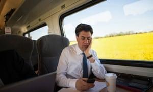 Ed Miliband checks his mobile phone.