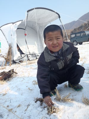 A young boy crouched down in the snow in front of a tent.