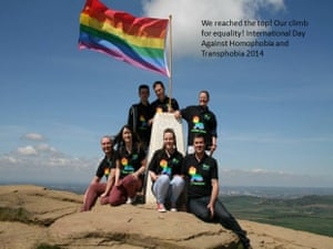 Group with gay pride flag on mountain top.