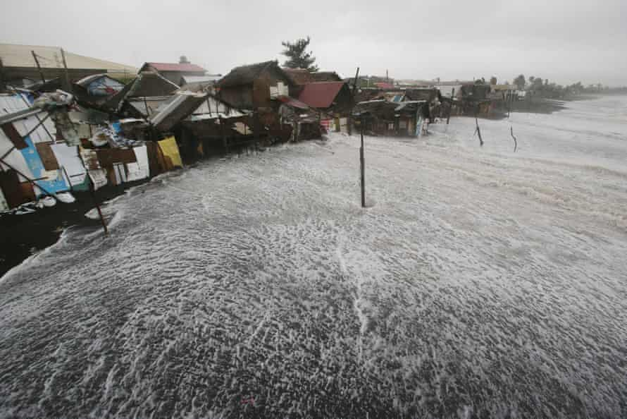 Waves crash into coastal houses as typhoon Hagupit pounds Legazpi, Albay province, eastern Philippines in December 2014.
