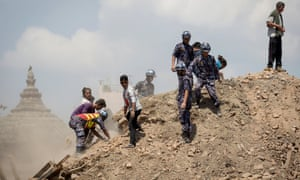 Nepalese police personnel and volunteers clear the rubble while looking for survivors at the compound of a collapsed temple, following the earthquake in Kathmandu, Nepal.