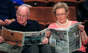 Snooker spectators reading the newspapers before day five of the world championships in Sheffield