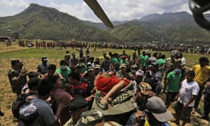 Nepalese soldiers carry a wounded woman to a waiting Indian air force helicopter as they evacuate victims from Trishuli Bazar to Kathmandu airport.
