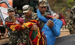 A victim with a broken leg from Saturday's massive earthquake is carried by Nepalese soldiers after arriving by helicopter from the heavily-damaged Ranachour village.