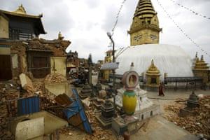 A monk walks past the badly damaged monastery and shrines at Swayambhunath