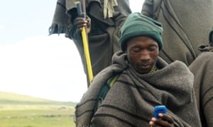 Lesothan shepherd using a mobile telephone