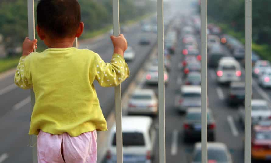 A child looks at a congested Beijing road. During the 2008 Olympics the government raised emissions standards and slashed the number of vehicles on the road.
