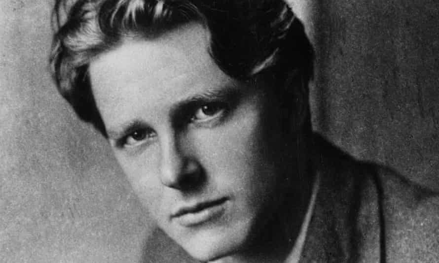 Rupert Brooke in a suit and tie, with a serious expression
