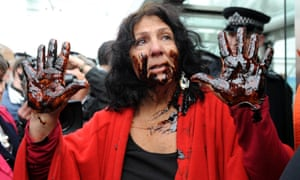 A protester daubs herself with oil as she tries to gain access to the BP AGM in London on 14 April.