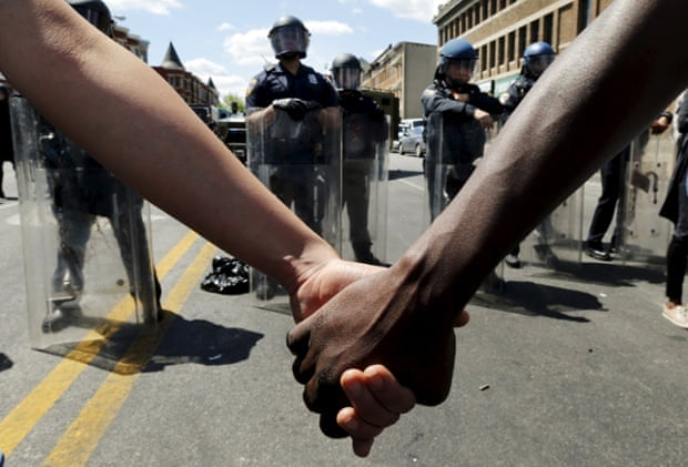 Members of the community hold hands in front of police officers in riot gear outside a recently looted and burned CVS store in Baltimore.