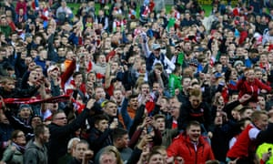 Rotherham fans celebrate on the pitch after seeing their side secure Championship safety.