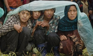 Villagers wait in the rain as an aid relief helicopter lands at their remote mountain village of Gumda, near the epicentre of the quake.