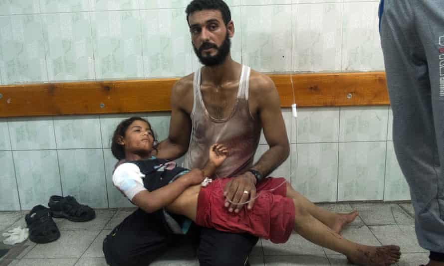A father comforts his daughter injured during an Israeli strike on the UN school at Beit Hanoun during the 2014 Gaza war.