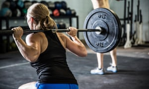 A woman does squats at a Crossfit gym.