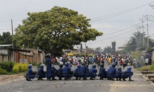 Burundi riot police face stone throwing demonstrators  during clashes in the Musaga district of Bujumbura, Burundi, Tuesday April 28, 2015. Anti-government street demonstrations continued for a third day after six people died in protests against the move by President Pierre Nkurunziza to seek a third term. (AP Photo/Jerome Delay)