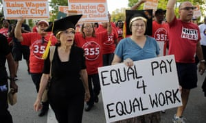 A woman carries a sign for equal pay as she marches with other Fight for 15 protesters in support of raising the minimum wage to $15 an hour.