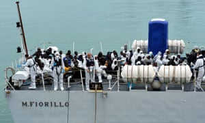 Rescued migrants wait before disembarking off the Italian Guardia Costiera vessel Fiorillo at the Sicilian harbour of Catania.