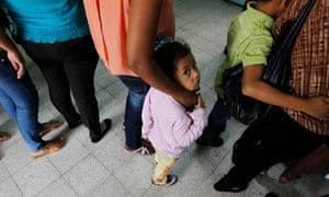 Women and their children wait in line at the Honduran Center for Returned Migrants.