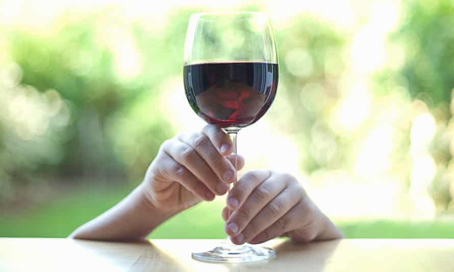 Little hands holding stem of wine glass
