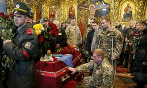 Ukrainian soldiers and coffin of comrade
